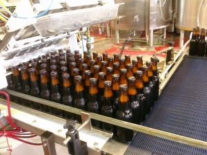 Filled and crowned bottles emerge from the Meheen on their way to the labeller
